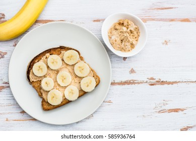 Healthy Snack Alternative made from Toasts from Wholewheat Bread with Peanut Butter and Banana with Cinnamon, Light Background