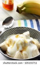 Healthy snack of Banana with yogurt and honey
