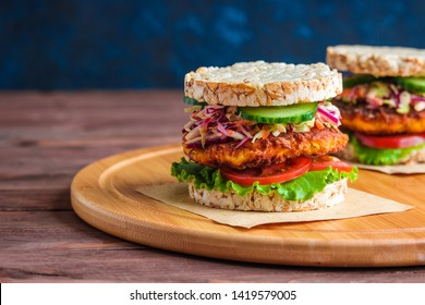 healthy snack burger with rice crackers carrot cutlet lettuce coleslaw tomato cucumber on round cutting board copy space