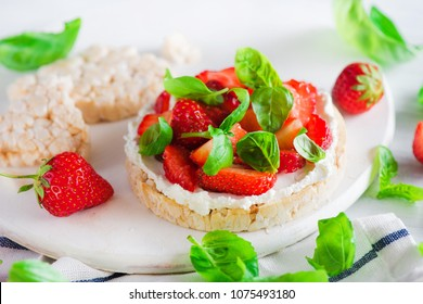 Healthy snack with crisp bread, fresh strawberries, goat cheese, and basil leaves. Easy appetizer recipe.