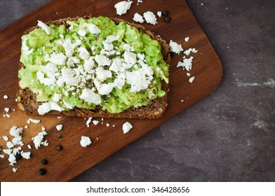 Healthy snack of dark rye bread topped with avocado and crumbled feta cheese served on a stone slate table top.