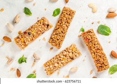 Healthy snack. Fitness. Dietary food. Four cereal granola bars with nuts and fruit berries, with ingredients on a white stone table. Top view copy space