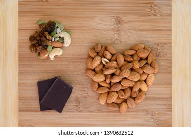 Healthy snack food choices including Almonds in the shape of a heart, Sultanas, Dark chocolate and seeds.