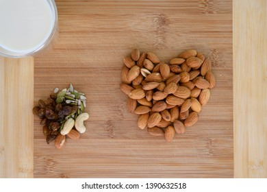 Healthy snack food choices including Fresh Milk in a glass, Almonds in the shape of a heart, Sultanas and seeds.