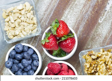 Healthy snack foods with small bowls of raspberries, blueberries, strawberries, cashews and walnuts - Shutterstock ID 211078603