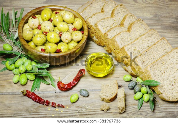 Healthy snack with fresh whole grain toast placed with pickles green and black olives, olive oil,raw olives and dry chili on rustic wooden table.Top view,copy space
