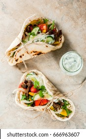 Healthy snack, lunch. Traditional Greek wrapped sandwich gyros - tortillas, bread pita with a filling of vegetables, beaf meat and sauce tzatziki. On light stone table Copy space top view