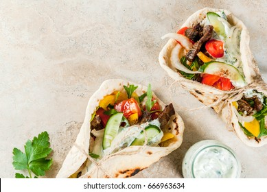 Healthy snack, lunch. Traditional Greek wrapped sandwich gyros - tortillas, bread pita with a filling of vegetables, beef meat and sauce tzatziki. On light stone table Copy space top view.