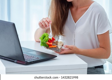 Healthy snack at office workplace. Business woman eating meals from lunch box at working table during lunch break. Food at work