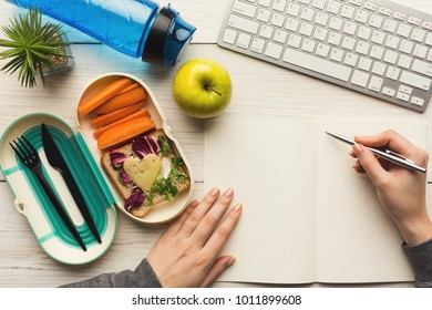 Healthy snack at office workplace. Businesswoman working and eating organic vegan meals from take away lunch box at wooden working table with computer keyboard, top view
