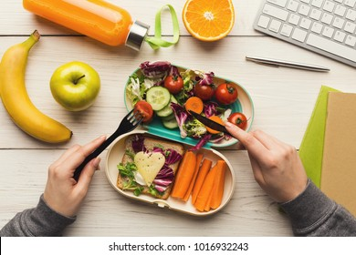 Healthy snack at office workplace. Businesswoman eating organic vegan meals from take away lunch box at wooden working table with computer keyboard