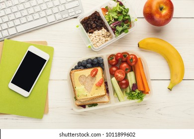 Healthy snack at office workplace. Eating organic vegan meals from take away lunch box at wooden working table with computer keyboard and smartphone with empty screen for copy space, top view