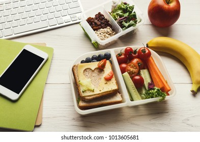 Healthy snack at office workplace. Organic vegetarian meals in take away lunch boxes at wooden working table with computer keyboard and smartphone
