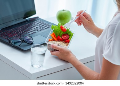 Healthy snack at office workplace. Worker eating food from take away lunch box at working table during lunch break