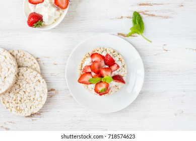 Healthy Snack from Rice Cakes with Ricotta and Strawberries on Light Wooden Background