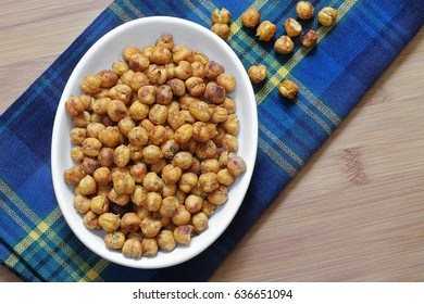 A healthy snack of roasted chick peas, garbanzo beans.  Top view, macro with copy space.