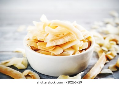 healthy snack: roasted coconuts chips in white ceramic bowl on white wooden table.