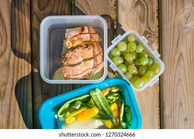 Healthy snack which consists of bread, grape, cheese and paprika in a plastic box on the wooden bench. Healthy lifestyle concept.