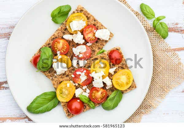 Healthy Snack from Wholegrain Rye Crispbread Crackers with Red and Yellow Cherry Tomatoes, Basil and Feta Cheese on the Light Background
