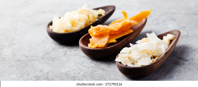 Healthy snacks. Dried mango, coconut chips and palm sugar in wooden bowls. Grey stone background. Copy space