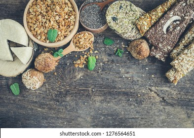 Healthy snacks. Fitness dietary food. Sesame halva. Flakes, chia seeds in two bowls and spoons. Kozinaki, energy bars and the breadsticks. Dietary cookie, mint. Old wooden board. Top view. Copy space.