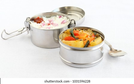 Healthy south Indian vegetarian lunch in two boxes of a lunchbox, with rice and sambar in one box, and curd rice in another box.