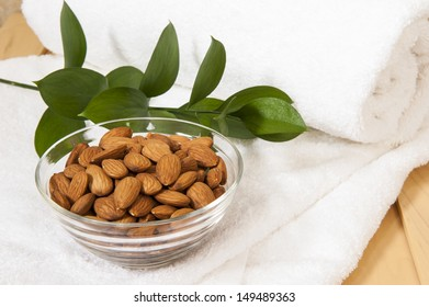 Healthy spa snack of a dish of almonds on a white towel