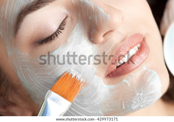 Healthy spa: young beautiful relaxing woman having moistening mask applied