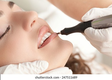 Healthy Spa: Young Beautiful Woman Having Permanent Make-up (Tattoo) on her Lips . Close-up .