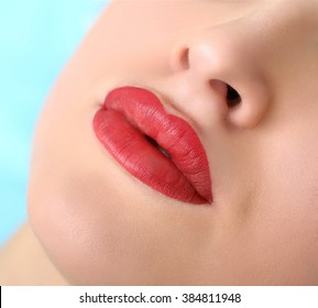 Healthy Spa: Young Beautiful Woman Having Permanent Make-up (Tattoo) on her Lips. Close-up