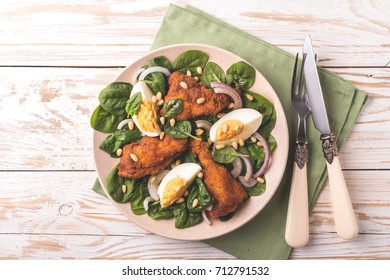 Healthy spinach salad with boiled egg, fried chiken, red onion and pine nuts. White wooden background