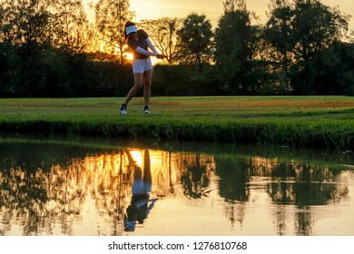 Healthy Sport. Asian Sporty woman golfer player chips and swing golf on the green outdoors sunset  evening time, she presumably does exercise.  Healthy Lifestyle Concept.