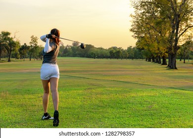 Healthy Sport. Asian Sporty woman golfer player doing golf swing tee off on the green outdoors evening time, she presumably does exercise.  Healthy Lifestyle Concept.