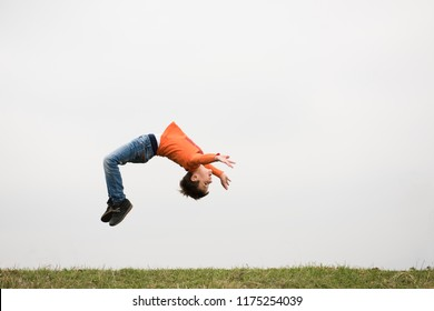 healthy sport little caucasian boy jumping somersault outdoors nature with copyspace