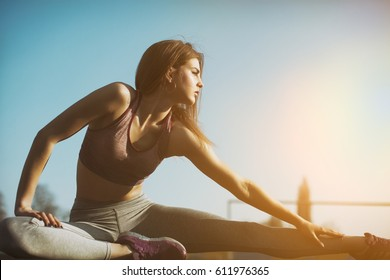 Healthy sports lifestyle. Athletic young woman in sports dress doing fitness exercise. Fitness woman on stadium.