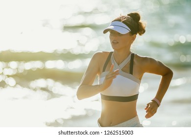 healthy sports woman in fitness clothes on the seashore in the evening jogging. seashore is perfect destination for mind, body and soul. sports woman take advantage of fresh air workout