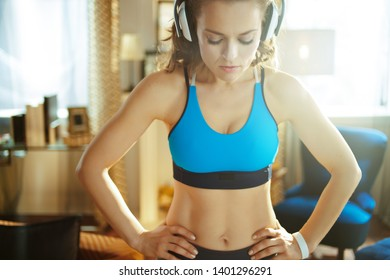 healthy sports woman in headphones in sport clothes in the modern house relaxing after workout.