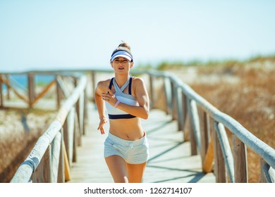 healthy sports woman in sport clothes on the seashore jogging. 30 something years old trying new seashore workouts. happy, healthy lifestyle