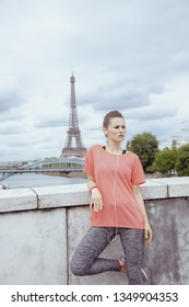 healthy sports woman in sport clothes listening to the music with headphones against Eiffel tower in Paris, France.