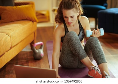 healthy sports woman in sport clothes with dumbbell using laptop to share workout results in social media at modern home.