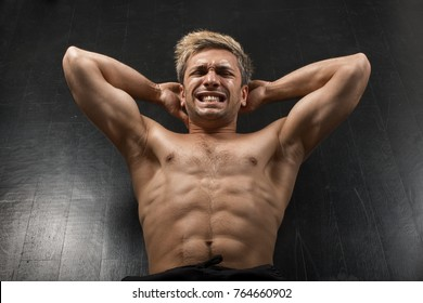 Healthy sportsman doing abs workout thru pain