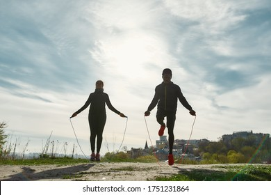 Healthy and sporty people. Young african fitness couple in sportswear exercising with skipping rope outdoors in nature against blurred city background. Sport, training, workout. Healthy lifestyle