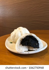 Healthy steamed bun pho stuffed with black bean on a plate with brown wooden blackground