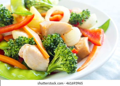 Healthy stir fried vegetables with chicken on white plate close up