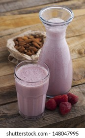 Healthy strawberry and almond milk on wooden table. Studio shot on daylight, shallow dept of field.