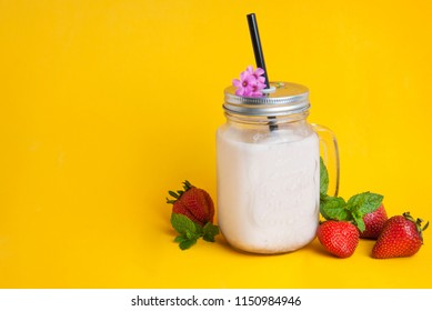 Healthy strawberry smoothie or drink yogurt in a mason a jar glass with berries and mint, over yellow background with copy space.