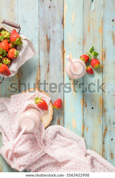Healthy strawberry smoothie in a mason glass jar with scattered fruits over a rustic wood background