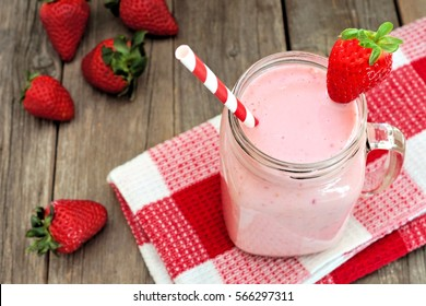 Healthy strawberry smoothie in mason a jar mug with checkered cloth against rustic wood