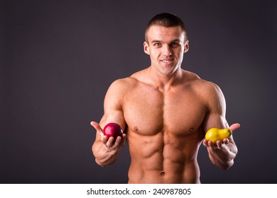 Healthy, strong man bodybuilder on a dark background, holding a fresh juicy fruits. Muscular guy holding apple and pear. Concept of healthy food, fruit, sports nutrition.