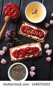 Healthy sugar free dessert and herbal tea. Raspberry chia jam on crispy bread and cream cheese with frozen berries on black background top view